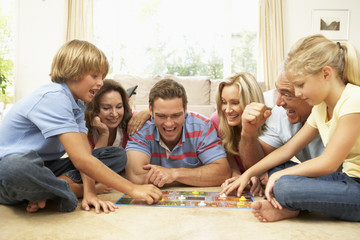 Family Playing Board Game At Home With Grandparents