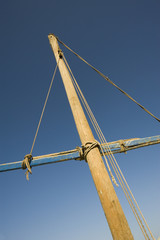 Old wooden mast on blue sky