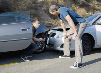 Two men examining damage in car collision
