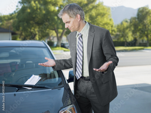 Frustrated businessman viewing parking ticket on windshield