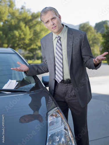 Frustrated businessman shrugging at parking ticket on windshield
