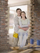 Couple hugging in doorway of house under construction