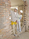 Couple standing in doorway of house under construction