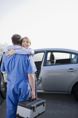 Woman hugging arriving mechanic