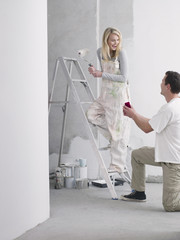 Man proposing to woman painting wall