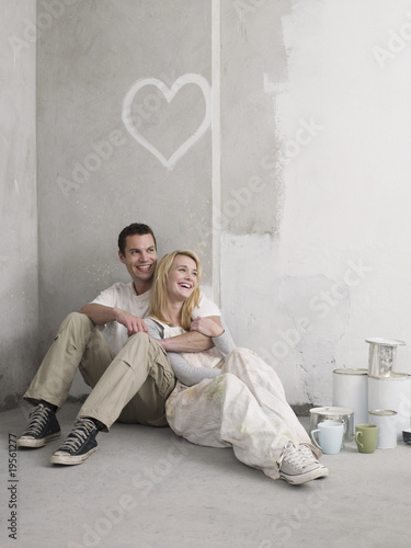 Couple sitting under painted heart on wall
