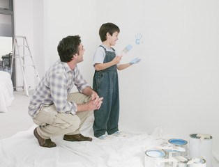 Father watching son make handprint on wall with paint