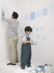 Father painting wall and boy putting handprints on wall