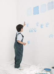 Boy putting handprints on wall with paint