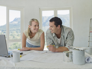 Couple leaning on table with blueprints and paint