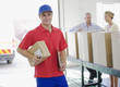 Delivery man holding cardboard box in warehouse