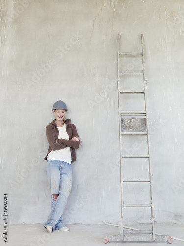 Woman wearing hard-hat and leaning against wall with ladder