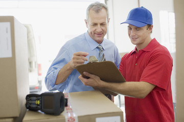 Businessman talking with delivery man in warehouse