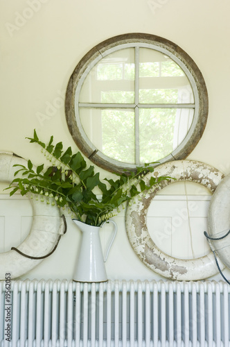 Vase and decor on radiator below mirror