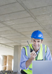 Worker talking on walkie-talkie on construction site