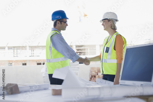 Co-workers shaking hands on construction site