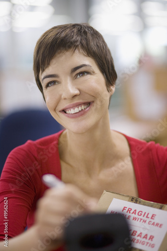 Businesswoman marking fragile box with marker