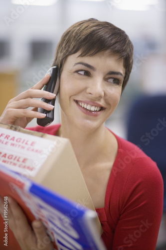 Businesswoman talking on phone and holding box