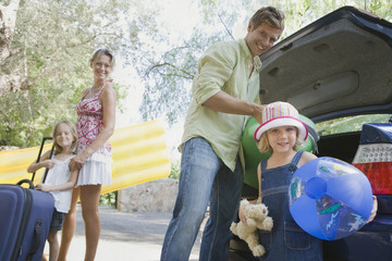 Family packing car with suitcases and beach toys