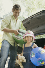 Father and daughter loading suitcase and beach ball into car trunk