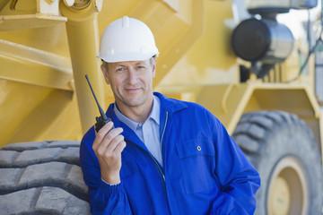 Construction worker talking on walkie-talkie near bulldozer