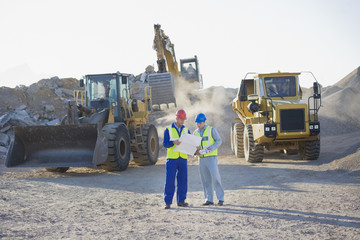 Construction workers and bulldozers on construction site