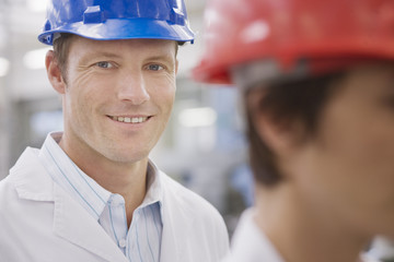 Man in hard-hat and lab coat smiling