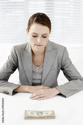 Businesswoman looking at stack of money