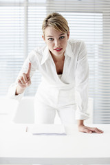 Businesswoman leaning on desk and gesturing with finger