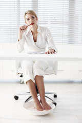Businesswoman soaking feet under desk