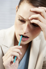 Businesswoman biting pencil