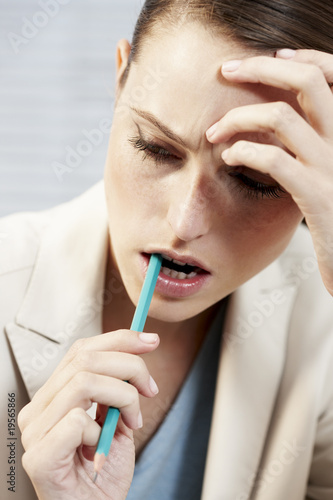 Businesswoman biting pencil