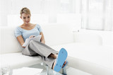 Businesswoman wearing flipflops and holding paperwork on sofa