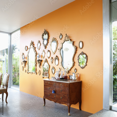Mirrors on orange wall