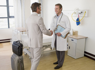Doctor greeting patient in hospital room