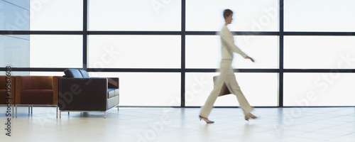 Businesswoman walking through office waiting area