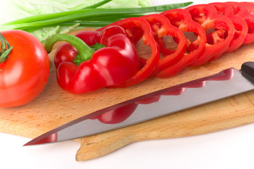 Sliced red ripe fresh pepper on cutting board with knife
