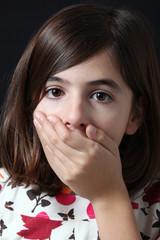 bambina stupita si copre la bocca