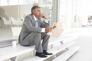 Mature businessman reading a newspaper