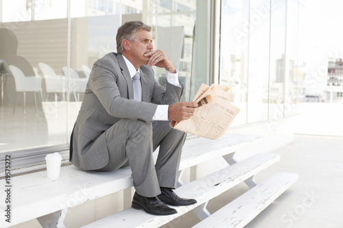 Mature businessman reading a newspaper