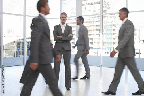 Girl standing among business people on the move
