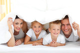 Fototapety Young family playing together on a bed