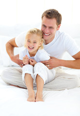 Attractive father playing with his little girl on a bed