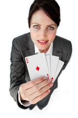 Charming businesswoman holding a full deck aces
