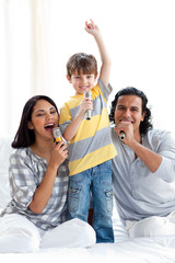 Lively young family singing with microphones