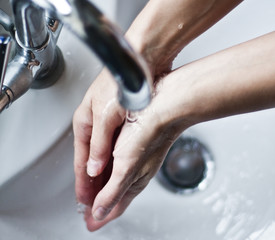 Washing hands under tap