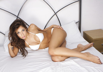 Young brunette woman on the bed wearing white bikini