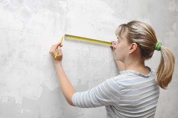 worker woman measuring on wall straightedgetape