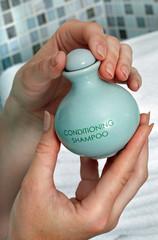 Green shampoo bottle in hand.