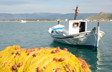 White boat and yellow fishing net with clear blue sea